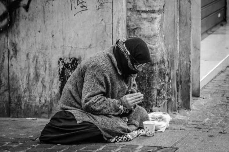 grayscale photography of man praying on sidewalk with food in front